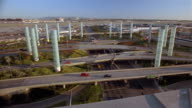 High angle long shot traffic passing circle of pylons at entrance to LAX / runway in background / Los Angeles
