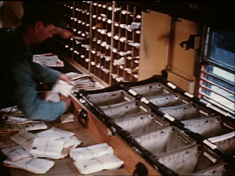 1958 high angle man sorting mail into different bins in mailroom