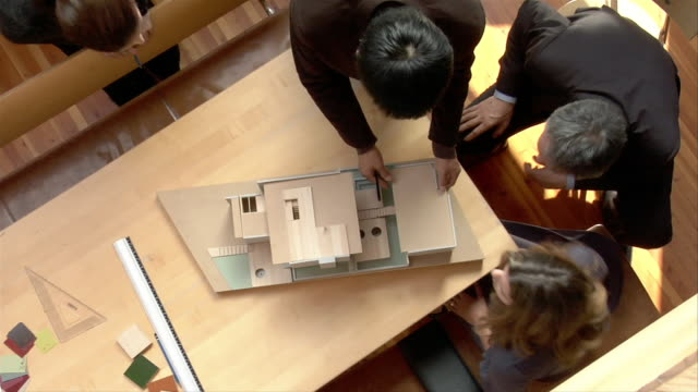 High angle medium shot architects and client surrounding table and looking at model