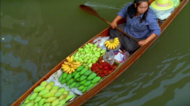 High angle medium shot Asian woman paddling boat filled with food at floating market / Damneon Saduak, Thailand