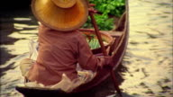 High angle medium shot Asian woman paddling boat with vegetables at floating market / Damneon Saduak, Thailand
