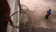 High angle medium shot boy shooting basketball at hoop and missing / running after ball
