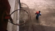 High angle medium shot boy shooting basketball at hoop and missing