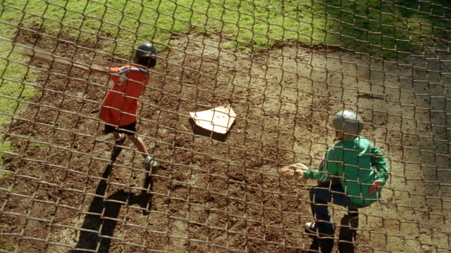 High angle medium shot boy swinging bat at ball and getting a hit / running towards first base