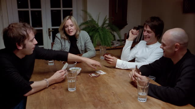 High angle medium shot dolly shot three men and a woman playing cards / man picking card + putting down 'gin' hand