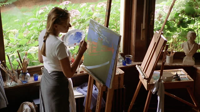 High angle medium shot female artist painting landscape on easel by window