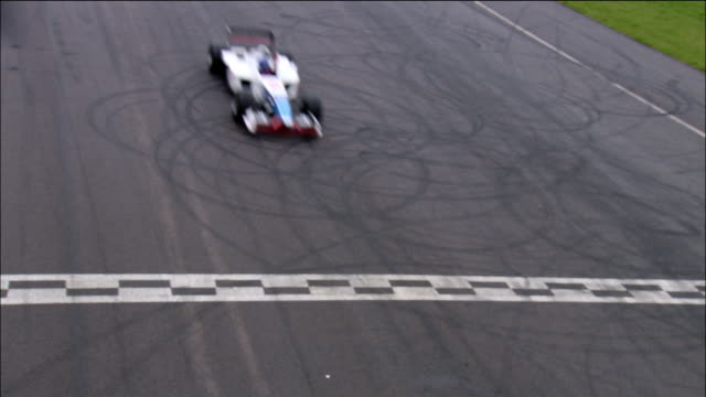 High angle medium shot Formula One race car crossing finish line with checkered flag waving in foreground