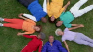 High angle medium shot group of seniors lying on grass in a circle holding hands
