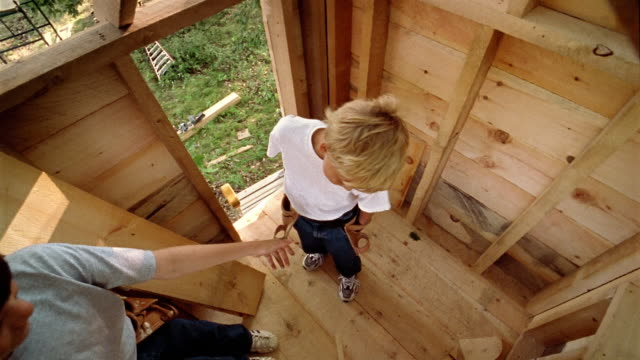 High angle medium shot little boy handing nail to older boy in treehouse