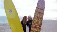 High angle medium shot man and woman holding surfboards + kissing