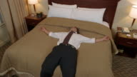 High angle medium shot man falling backwards onto bed / sitting up and looking around hotel room