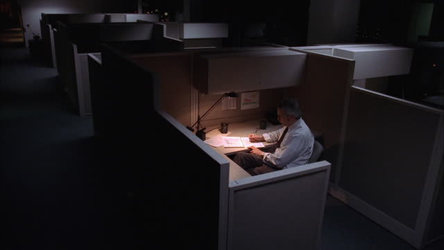 High angle medium shot man working at desk in cubicle in dark empty office
