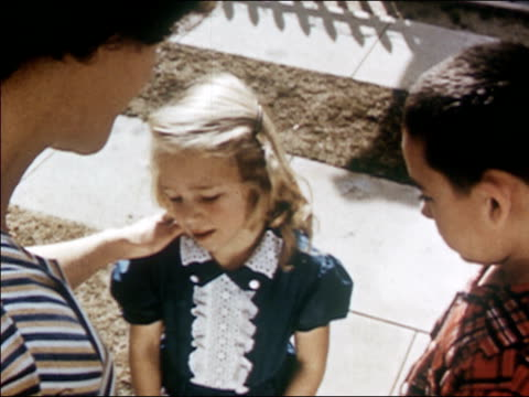 1954 High angle medium shot mother scolding little girl / pan boy and girl walking away together