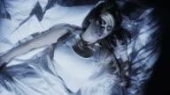 High angle medium shot of nightmare projections on sleeping woman / Cedar Hills, Utah, United States
