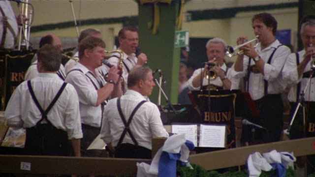 High angle medium shot oom-pah band performing on bandstand in pavilion at Oktoberfest / Munich, Germany