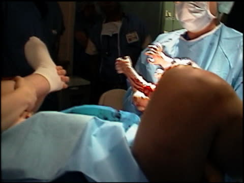 High angle medium shot pan doctor delivering baby and handing baby to mother / medical staff cleaning off baby