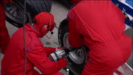High angle medium shot pan pit crew members changing tires on Formula One race car