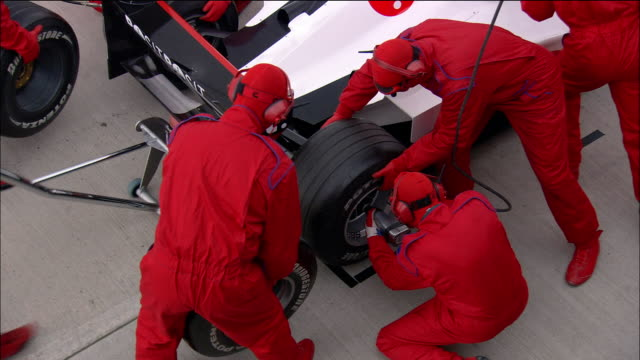 High angle medium shot pit crew members changing tire on Formula One car during pit stop / congratulating each other