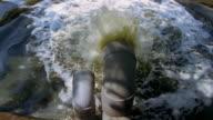High angle medium shot sewer pipe spraying into water / Jakarta