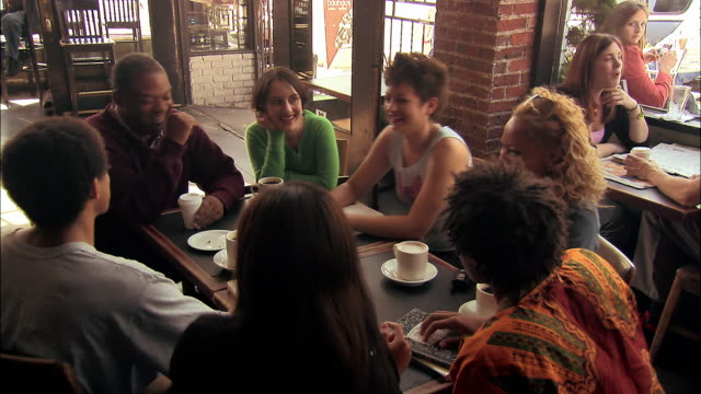 High angle medium shot study group engaged in discussion with professor in coffeehouse / Seattle