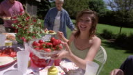 High angle medium shot teenage girl passing bowl of strawberries to family seated at table