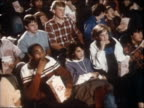 1985 high angle medium shot Teens sitting in a movie theater and eating popcorn