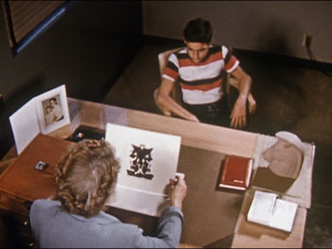 1955 high angle medium shot therapist administering Rorschach inkblot test to young teenage boy