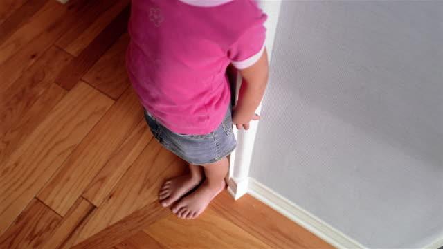 High angle medium shot tilt up girl measuring her height