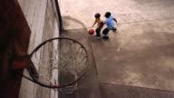High angle medium shot two young boys playing one-on-one basketball / boys shooting ball