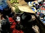 High angle medium shot woman buying produce at market/ Ghana