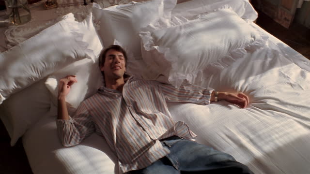 High angle medium shot young man in button-down shirt and jeans falling onto bed / relaxing + smiling