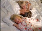 high angle mother in bed with twin blonde daughters in pajamas