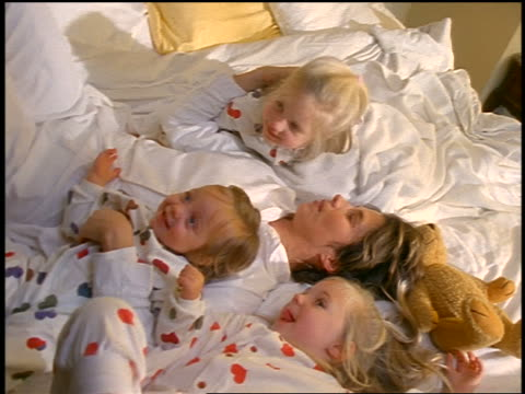 high angle mother playing in bed with baby + twin blonde daughters in pajamas