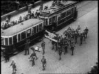 B/W 1927 high angle Nazis parading with signs past trolley on cobblestone street at Nuremberg rally / newsreel