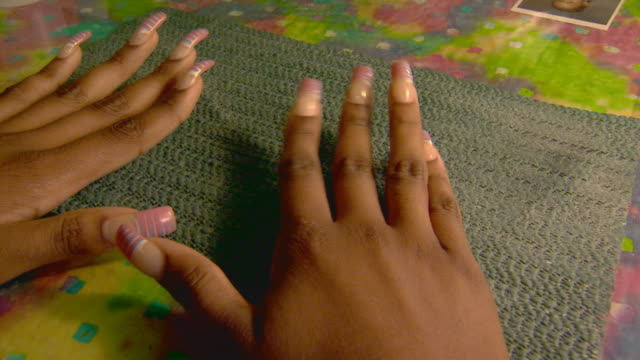 High angle of a woman giving a manicure to another woman, handheld shot