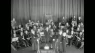 LS high angle of conductor/composer John Philip Sousa musician Arthur Pryor and composer/conductor Edwin Franko Goldman on stage in front of band SOT...