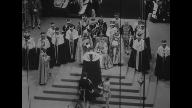 High angle of Elizabeth seated on the Chair of Estate watches as Prince Philip removes his crown hands it to a page walks up steps bows to her and...