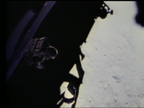 high angle of John Young stepping off lunar lander onto Moon