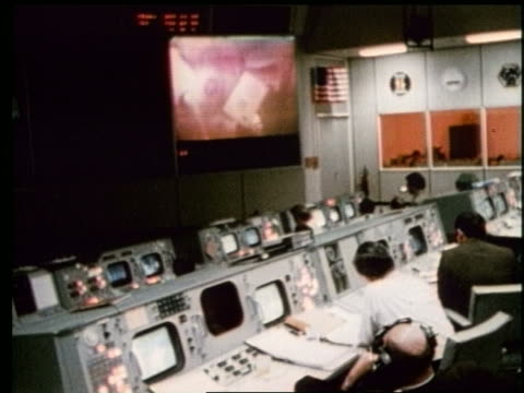 high angle of men at controls watching astronauts on screen