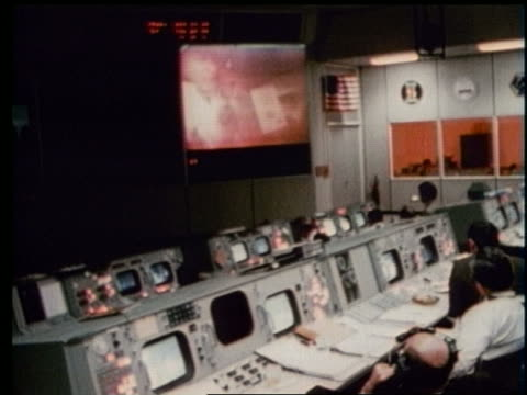 high angle of men at controls watching screen at Mission Control
