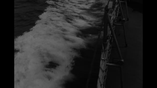 MS high angle of wake alongside side of ship cutting thru water / MLS ship's wake viewed from rear of ship / MS ship's guns and upper decks