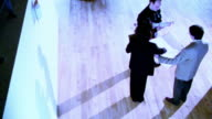 BLUE OVEREXPOSED high angle PAN one female + two male architects holding blueprints + talking in empty room