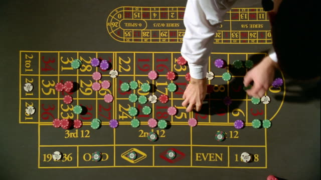 High angle pan croupier and gambler placing chips on roulette table / croupier spinning roulette wheel
