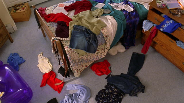 High angle pan messy bedroom with clothes lying on bed and floor