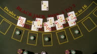 High angle pan overhead view of dealer dealing blackjack hands / taking away losing bets