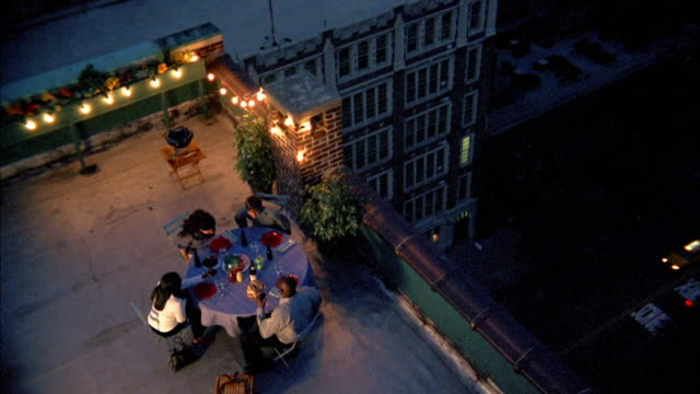 High angle people having dinner on rooftop w/buildings in background / NYC