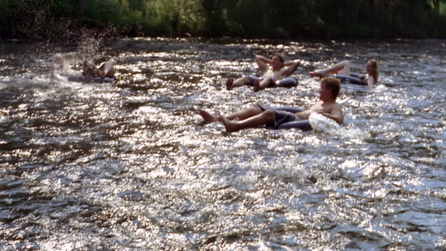 High angle people riding innertubes on river