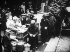 B/W 1929 high angle people standing in line at outdoor soup kitchen / Great Depression / newsreel
