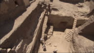 High Angle, push-in tilt-down - Excavators descend stairs in a ruins / Egypt