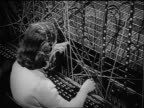 B/W 1946 high angle REAR VIEW female telephone operator plugging cables into switchboard